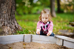 Adorable girl playing in a sandbox Stock Photography