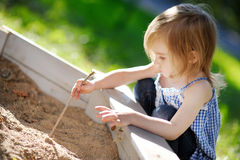 Adorable girl playing in a sandbox Stock Photos