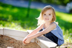Adorable girl playing in a sandbox Stock Images