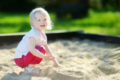 Adorable girl playing in a sandbox Stock Photos