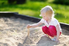 Adorable girl playing in a sandbox Royalty Free Stock Photography