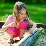 Adorable girl playing in a sandbox Stock Image