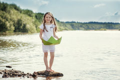 Adorable girl posing with paper boat on lake Stock Image