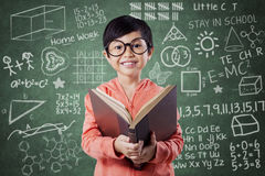 Adorable girl reads book near the blackboard Stock Images