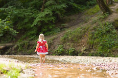 Adorable girl in red dress walk in river Royalty Free Stock Photo