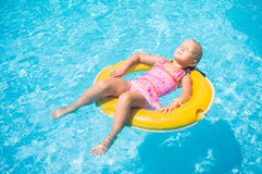 Adorable girl relax on yellow life ring in pool at protical beac Stock Photography