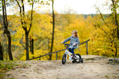 Adorable girl riding a bike on an autumn day Stock Image