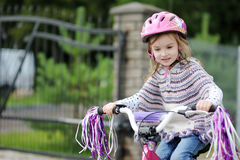 Adorable girl riding a bike on autumn day Stock Images