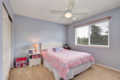 Adorable girl's room with pink bedding and soft lavender walls. Royalty Free Stock Photos