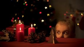 Adorable girl secretly looking wooden toys, Christmas tree twinkling, childhood. Stock photo royalty free stock image