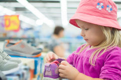 Adorable girl selecting shoes in supermarket Royalty Free Stock Photos