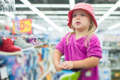 Adorable girl selecting shoes in supermarket Stock Photo