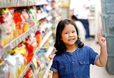 Adorable girl at shelves in supermarket. Stock Photos