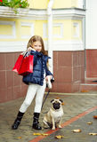 Adorable girl with shopping bags and her dog. Fancy little girl after shopping with red bags and her pug Royalty Free Stock Images