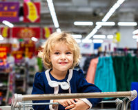 Adorable girl in shopping cart Stock Images