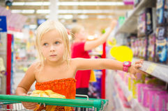 Adorable girl in shopping cart looks at goods on shelves in supe Stock Photography