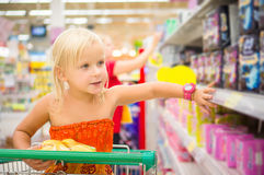 Adorable girl in shopping cart looks at goods on shelves in supe Royalty Free Stock Image