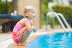 Adorable girl sit on pool side in tropical beach resort Royalty Free Stock Photography