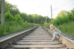 Adorable girl sit on rail wait for train Stock Images