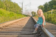 Adorable girl sit on rail wait for train Royalty Free Stock Image