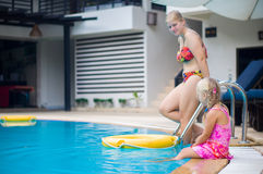 Adorable girl sit on side and mother going down the ladder to sw. Imming pool in tropical beach resort Royalty Free Stock Photo