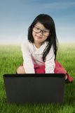 Adorable girl sits on the grass with laptop Royalty Free Stock Images