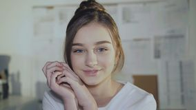 Adorable girl sits at workplace, leans on hands and smiles at camera. stock footage