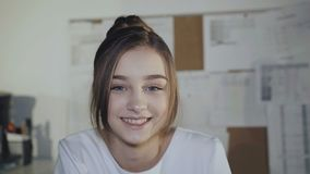 Adorable girl sits at workplace, leans on hands and smiles at camera. stock video footage