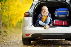 Adorable girl sitting ain a car trunk ready to go on vacations with her parents. Child looking forward for a road trip or travel. Royalty Free Stock Photos