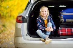 Adorable girl sitting ain a car trunk ready to go on vacations with her parents. Child looking forward for a road trip or travel. Royalty Free Stock Photo