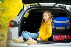 Adorable girl sitting ain a car trunk ready to go on vacations with her parents. Child looking forward for a road trip or travel. Stock Image