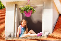 Adorable girl sitting on the ledge of attic window stock photos