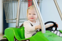 Adorable girl sitting in shopping cart Stock Photography