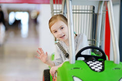 Adorable girl sitting in shopping cart Stock Images