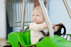 Adorable girl sitting in shopping cart Royalty Free Stock Photography