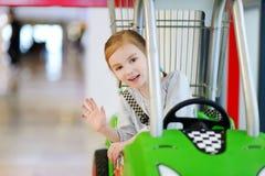 Adorable girl sitting in shopping cart Royalty Free Stock Photos
