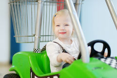 Adorable girl sitting in shopping cart Stock Photo