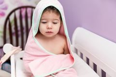 Adorable Girl Sitting Under Hooded Towel After Bath. Cute female toddler wearing hooded towel while sitting in crib stock photography
