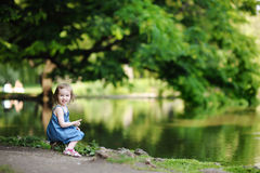 Adorable girl sitting by the water Royalty Free Stock Images