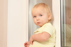 Adorable girl sitting on the window sill Royalty Free Stock Photos