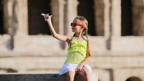 Adorable girl with small toy model airplane background Colosseum in Rome, Italy. Young girl in front of colosseum in rome, italy stock footage
