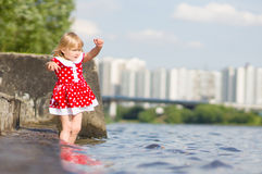 Adorable girl stay in water on pier ladder Royalty Free Stock Photos