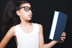 Adorable girl studying with eyeglasses and book in hand Stock Image