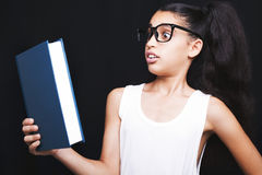 Adorable girl studying with eyeglasses and book in hand Royalty Free Stock Photo