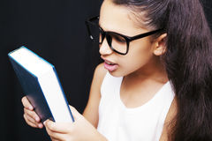 Adorable girl studying with eyeglasses and book in hand Stock Photography