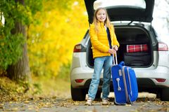 Adorable girl with a suitcase ready to go on vacations with her parents. Child looking forward for a road trip or travel. Autumn b Royalty Free Stock Images
