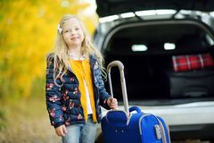Adorable girl with a suitcase ready to go on vacations with her parents. Child looking forward for a road trip or travel. Autumn b Royalty Free Stock Photography