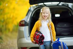 Adorable girl with a suitcase ready to go on vacations with her parents. Child looking forward for a road trip or travel. Autumn b. Reak at school. Traveling by Stock Photos
