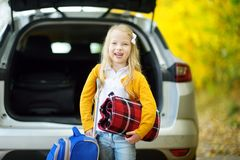 Adorable girl with a suitcase ready to go on vacations with her parents. Child looking forward for a road trip or travel. Autumn b. Reak at school. Traveling by Royalty Free Stock Photography