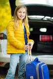 Adorable girl with a suitcase ready to go on vacations with her parents. Child looking forward for a road trip or travel. Autumn b. Reak at school. Traveling by Stock Images